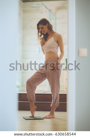 Young woman standing on bathroom. Woman Bathroom Standing On Weight Scale Stock Photo 606320111
