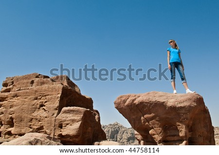 young woman standing on big rock with blue sky in background