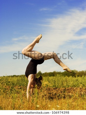 Young woman standing on her hands outdoors - stock photo