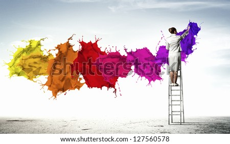 Young woman standing on ladder drawing splashes with finger - stock photo