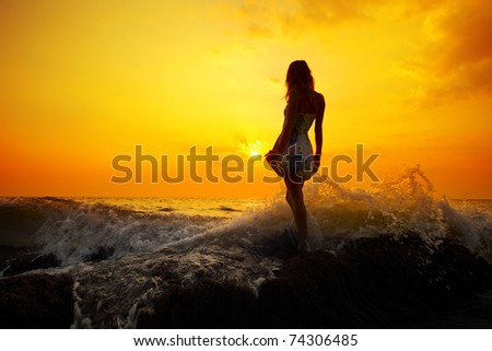Young woman standing on rock in sea and holding her dress. - stock photo
