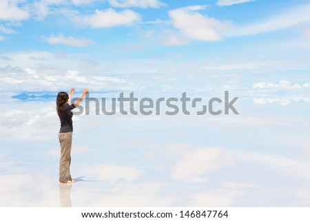 Young woman standing on Salar de Uyuni with raised hands - stock photo