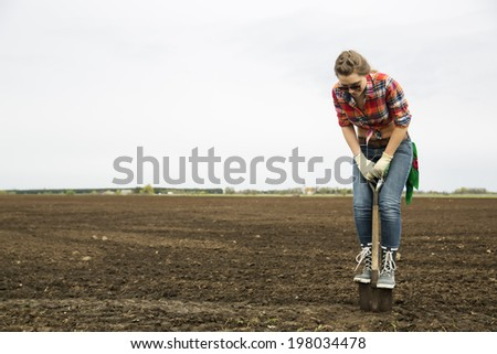 Young woman standing on sharp shovel looking down - stock photo