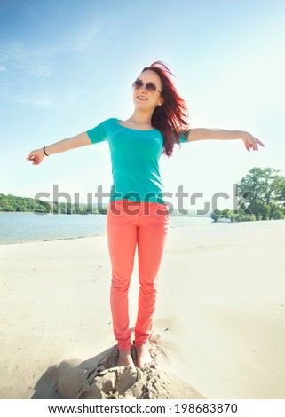 Young woman standing on the beach with arms outstretched, feeling happy. - stock photo