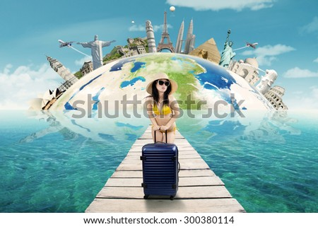 Young woman standing on the bridge while wearing swimsuit and carrying bag to holiday on the worldwide monument - stock photo
