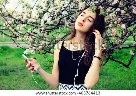 Young woman standing on the meadow at the blooming tree , using smartphone to listening music with headphone