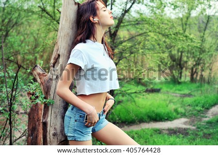 Young woman standing on the meadow at the old dead tree , using smartphone to listening music with headphone  - stock photo