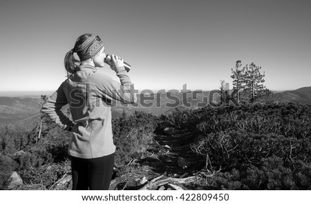 Young woman standing on top of the mountain enjoying sunny day and looking on mountain valley below. Tourist wearing pink jacket drinking tea out of thermos. black and white - stock photo