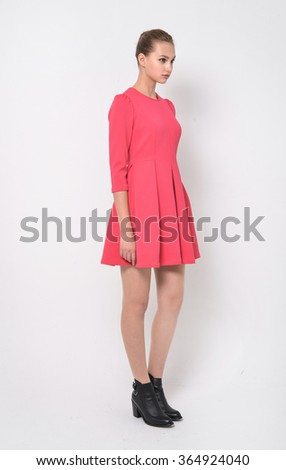 Young woman standing posing against on white background - stock photo