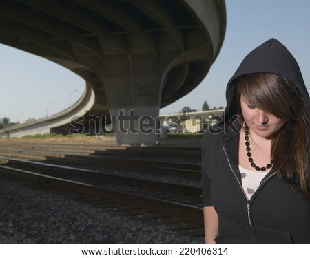 Young woman standing under raised highway - stock photo