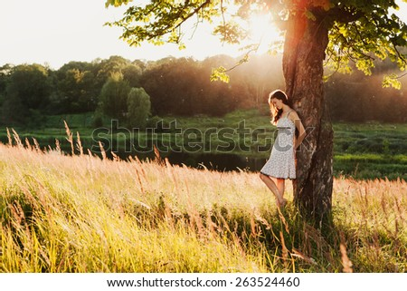 young woman standing under the tree, summer sunset