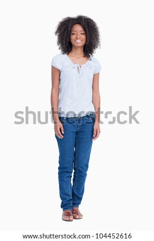 Young woman standing upright while beaming against a white background