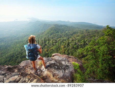 Young woman standing with backpack on cliff's edge and looking to the horizon - stock photo