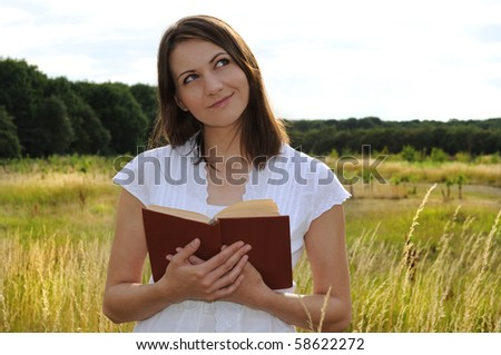Young woman standing with book in field - stock photo