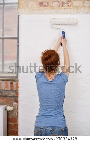 Young woman standing with her back to the camera painting a white wall with a roller in a DIY and renovation concept - stock photo