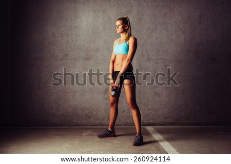 Young woman standing with kettlebell. Cross workout - stock photo