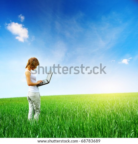 Young woman standing with laptop on a green meadow - stock photo
