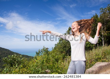 Young woman stands on a hilltop points into the distance  - stock photo