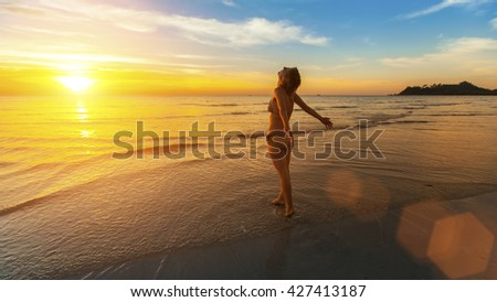 Young woman stands on the beach welcoming the dawn.
