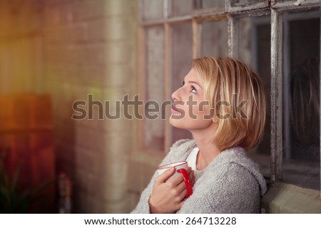 Young woman staring dreamily into the air as she sits on a sofa at home clutching a cup of coffee to her chest - stock photo