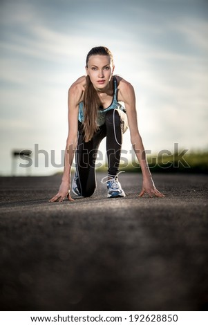 Young woman start running on auto road during sunset. backlit - stock photo