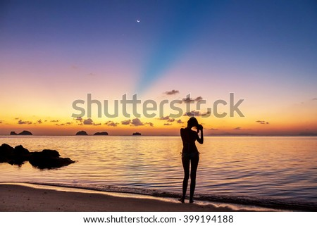 Young woman stay on the beach  and watching the sunset on a tropical island Koh Samui, Thailand. Colored reflections in water and sunbeam in background