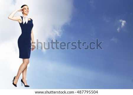 Young woman stewardess in full growth salutes against the sky with clouds and sun beam.