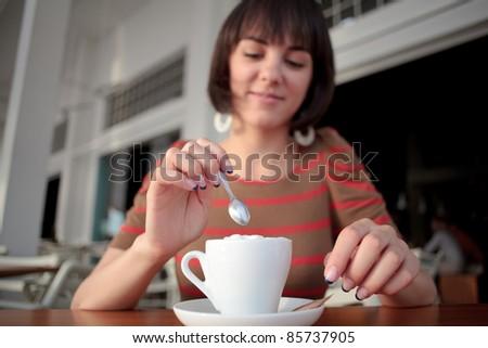 young woman stirring coffee - stock photo