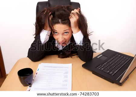 Young woman stressed at work in a black suit - stock photo