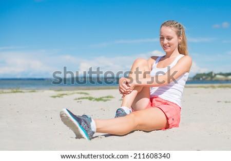 Young woman stretches before doing sports. - stock photo