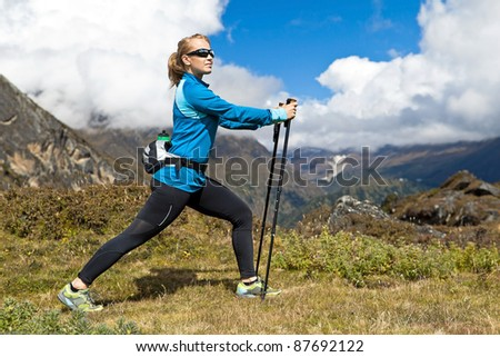 Young woman stretching and nordic walking in Himalaya Mountains in Nepal - stock photo