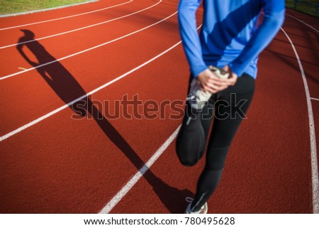 Young woman stretching before her run casts a shadow on the track
