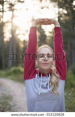 Young woman stretching before running in the early evening - stock photo