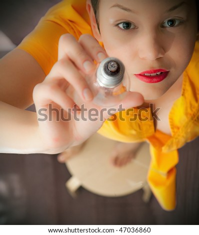 young woman, stretching hand up with light bulb - stock photo
