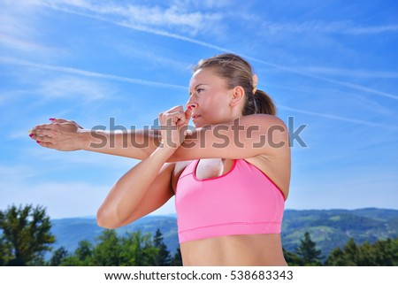 Young woman stretching her arms up while exercising on a mountain