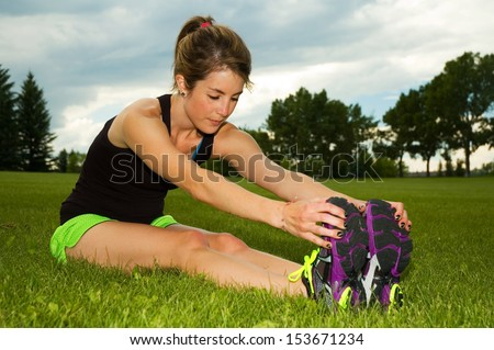 Young woman stretching her hamstrings in a park.