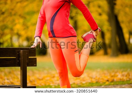 Young woman stretching her leg at bench before jogging in autumn nature - stock photo