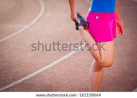 Young woman stretching her leg before her run (color toned image) - stock photo