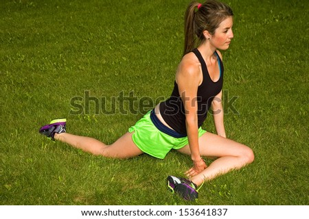 Young woman stretching her legs.