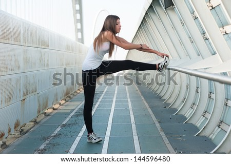 Young woman stretching her legs outdoors in modern environment. - stock photo