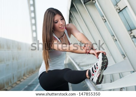 Young woman stretching her legs outdoors in modern environment.