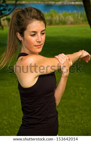 Young woman stretching her shoulder blade. - stock photo