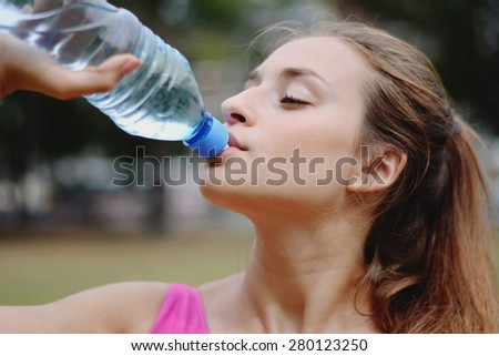Young woman stretching in the park and drinking water before Exercise. Caucasian sport fitness model in city park outdoors. - stock photo