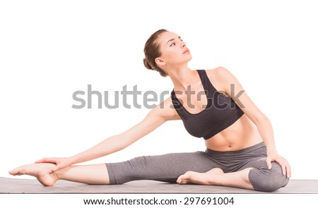 Young woman stretching in yoga position and looking away at the studio. - stock photo