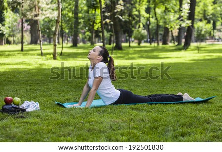 Young woman stretching on a green mat outdoor in a park.