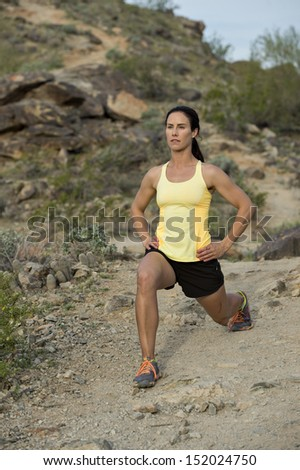 Young woman stretching to warm up for a trail run outdoors at South Mountain Park in Phoenix, Arizona.