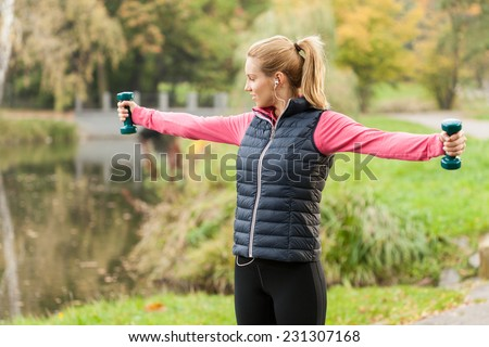 Young woman stretching with weights during morning jogging - stock photo