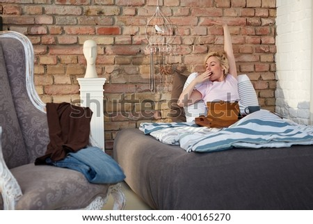 Young woman stretching, yawning in bed in the morning. - stock photo