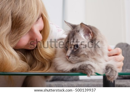 young woman stroking ragdoll cat
