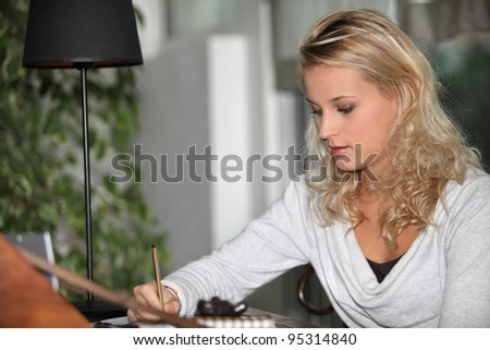 Young woman student doing homework - stock photo